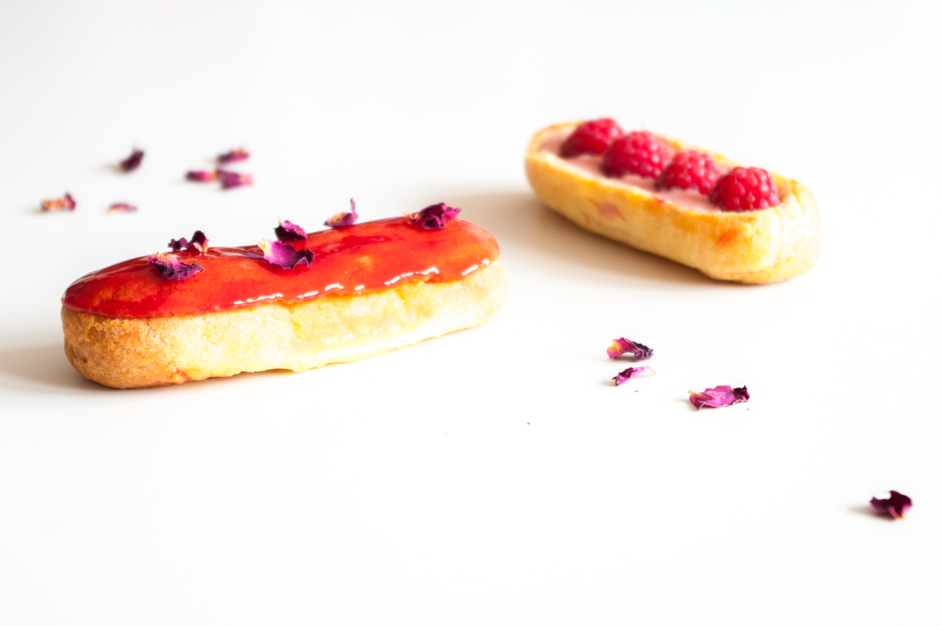Raspberry Éclairs with Rose Recipe – These raspberry éclairs are filled with fresh raspberry and rose pastry cream and topped with a raspberry glaze and dried rose petals. By @deliciouscratch | deliciousfromscratch.com
