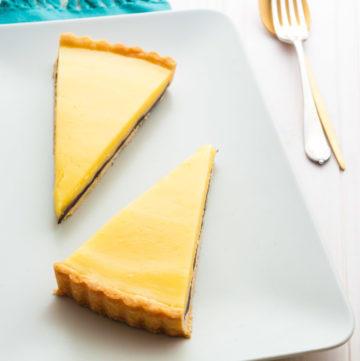 Lemon Tart with the Surprise! This French lemon tart recipe is made with homemade sweet pastry and tangy lemon curd, with a surprise layer of bitter dark chocolate to balance the sweetness. A spectacular celebration dessert for a crowd. By @deliciouscratch | deliciousfromscratch.com
