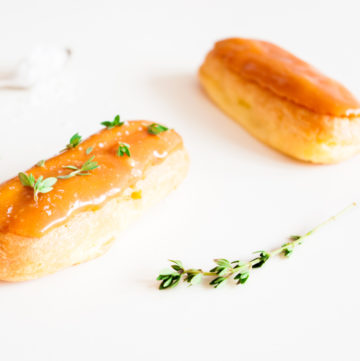 Salted Caramel Éclairs – These salted caramel éclairs are filled with salted caramel pastry cream and topped with a salted caramel glaze and lemon thyme. An elegant party dessert recipe. By @deliciouscratch | deliciousfromscratch.com