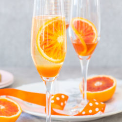 Blood orange fizz cocktail recipe – blood orange syrup, fresh blood oranges and sparkling white wine. The perfect spring cocktail!